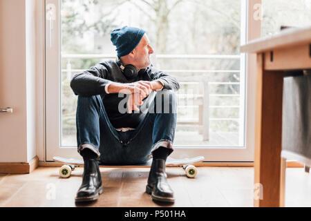 Cool man assis sur le sol, à la fenêtre de Banque D'Images
