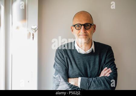 Portrait d'un homme staning en face du mur avec les bras croisés Banque D'Images