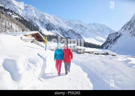Couple marchant dans un paysage couvert de neige Banque D'Images