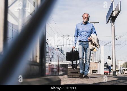Mature businessman walking à quai avec valise et porte-documents Banque D'Images