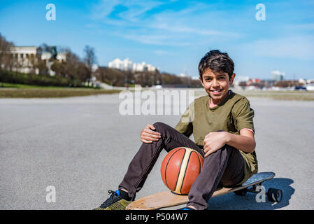 Portrait of smiling boy with longboard et de basket-ball extérieur Banque D'Images
