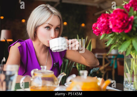 Pretty woman drinking herbal tea in restaurant Banque D'Images