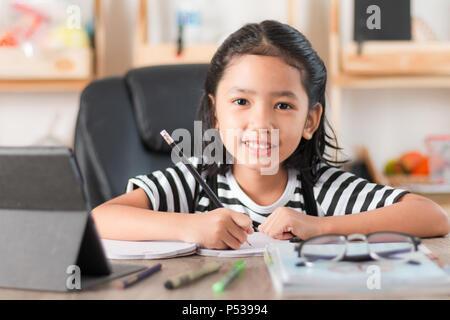 Petite fille asiatique à faire des devoirs et en pointant le doigt sur table en bois sélectionner focus profondeur de champ Banque D'Images