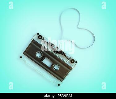 Cassette audio translucide avec la bande magnétique en forme de coeur isolé sur fond bleu, musique amour concept Banque D'Images