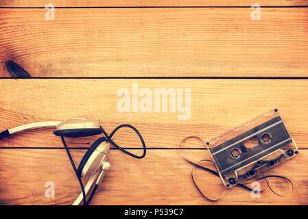 Écouteurs et translucide sur cassette audio vintage plancher bois blanc fond copy space