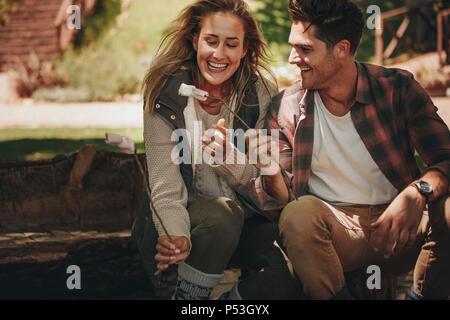 Camping Smiling young woman eating sweets rôti. L'homme et la femme ayant des guimauves grillées sur le camping. Banque D'Images