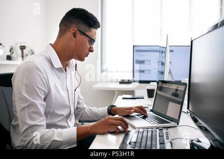 Développeur logiciel assis à son bureau travaillant sur ordinateur portable portant des écouteurs. Homme portant des lunettes working on laptop computer in office. Banque D'Images