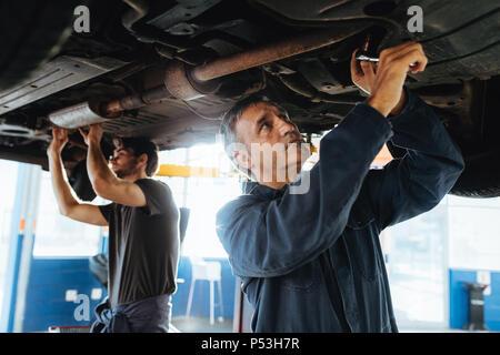 Deux mécaniciens travaillant sous une voiture. Les hommes en garage de réparation d'un système d'échappement automobile levé. Banque D'Images