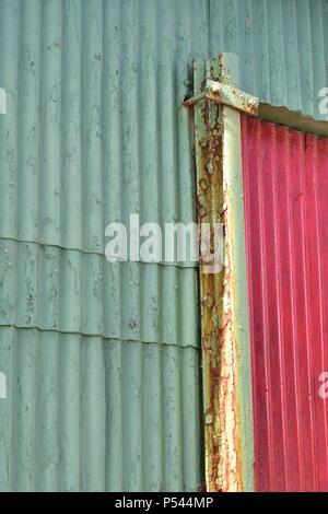 Le vert pâle et rouge mur extérieur fabriqués à partir de tôle ondulée avec quelques taches de rouille. Banque D'Images
