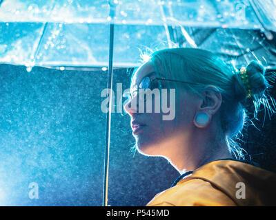 Très jolie fille aux cheveux teints en bleu imperméable jaune et transparent avec des socles de parasol près de la fontaine. Néon nuit de ville. Portrait de hipster élégant avec des lunettes. Banque D'Images