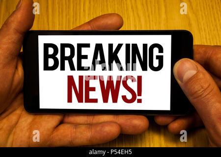 Signe texte montrant les Dernières Nouvelles Appel de motivation. Photo conceptuel mis à jour rapport de presse Dernières informations deux mains tenant l'écran téléphone noir paroles Banque D'Images