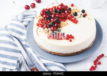 New York cheese cake aux fruits rouges sur la table en bois blanc. Vue d'angle. Banque D'Images