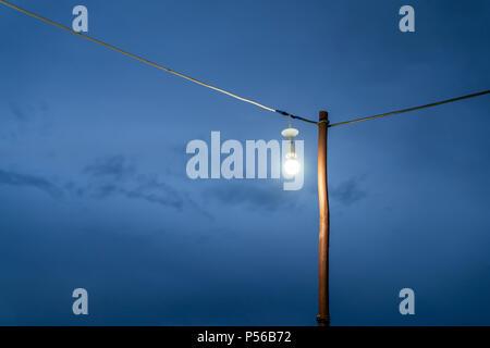 Ampoule à incandescence ouvert avec de vieux fils électriques, ciel sombre au crépuscule Banque D'Images
