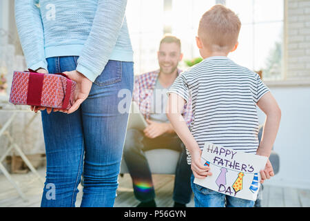 Retour Voir portrait de jeune femme et petit garçon surprenant papa pour la fête des Pères en lui donnant des cadeaux et cartes de vœux faits à la main Banque D'Images