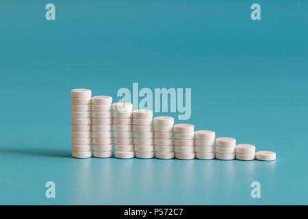 Une pile de pilules sur un fond bleu. Graphique de croissance fait de pilules blanches empilées - croissance du marché et de la demande croissante de comprimé blanc et c'est substit Banque D'Images