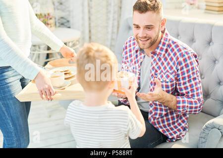 Portrait aux teintes chaleureuses du beau jeune homme à la tendresse à son fils lui donnant le présent et petit-déjeuner surprise pour la fête des pères à la maison, copy space Banque D'Images