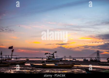 Silhouette de bateaux de pêche à marée basse, le coucher du soleil près de Mahim bay - Mumbai, Maharashtra, Inde. Et Worli Link, Bandra Pali Hill dans l'arrière-plan. Banque D'Images
