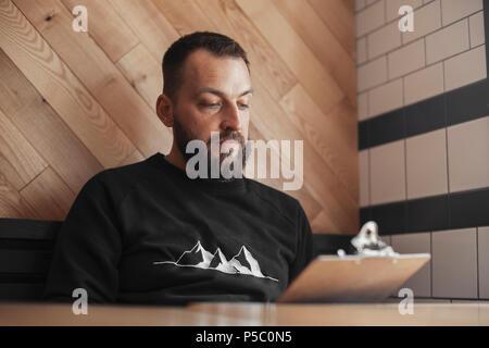 Jeune hipster tatouée menu holding au café. Banque D'Images