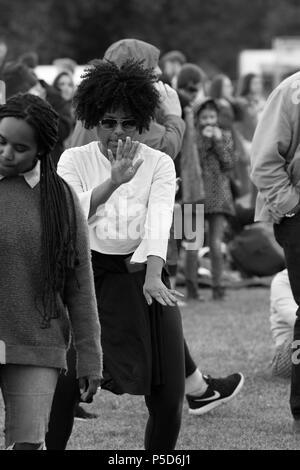 L'image monochrome candide d'une belle noire avec des cheveux bouclés à danser à l'Afrique 2018 Oye music festival à Sefton Park, Liverpool. Banque D'Images