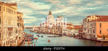 Classic vue panoramique de célèbre Canal Grande avec scenic Basilica di Santa Maria della Salute dans la belle lumière du soir au coucher du soleil d'or avec retro Banque D'Images