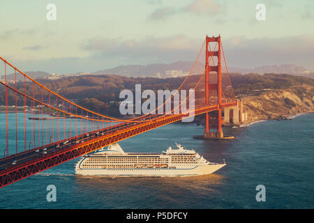 Belle vue panoramique de navire de croisière passant célèbre Golden Gate Bridge avec la skyline de San Francisco en arrière-plan dans la belle golden eveni
