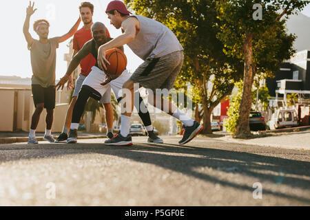 Les hommes jouant au basket-ball jeu sur une journée ensoleillée sur une rue vide. Les hommes pratiquant le basket-ball ses dribbles sur rue.