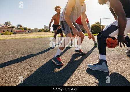 Les hommes jouant au basket-ball jeu sur une journée ensoleillée. Les hommes exerçant des compétences de basket-ball dans l'aire de jeu.