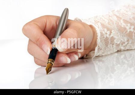 La main élégante écrit avec un stylo à plume d'or Banque D'Images