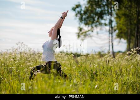 Young woman practicing yoga piscine dans parc. Banque D'Images