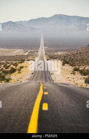 Classic vue panoramique de une interminable route droite qui traverse les paysages arides du sud-ouest américain avec la Brume de chaleur extrême sur une belle s Banque D'Images