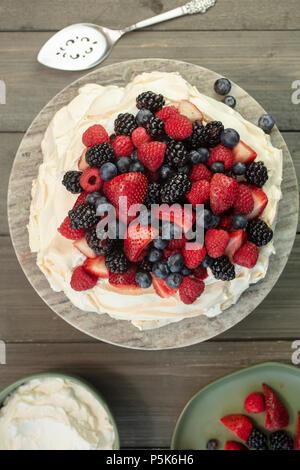 Pavlova gâteau meringue dessert à base de fraises, mûres, framboises et bleuets, plantés sur une plate-forme de granit Banque D'Images