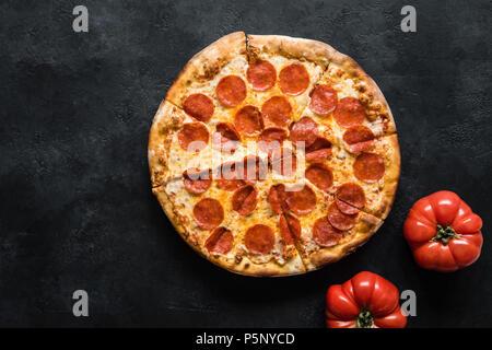 Pizza au pepperoni, sur fond de béton noir. American pizza au pepperoni, vue du dessus Banque D'Images