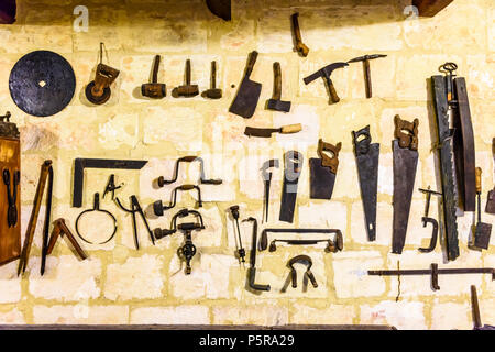 Vieux outils traditionnels accroché sur un mur dans un atelier de travail du bois. Banque D'Images