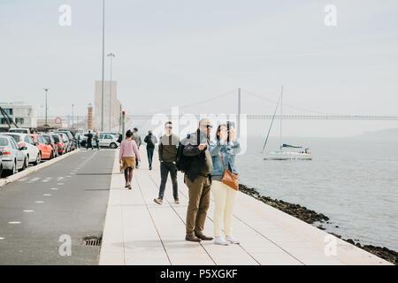 Lisbonne, 1 mai, 2018: un couple d'hommes et de femmes font un dans le secteur riverain de selfies Belem. Les gens se promènent autour. Dans l'arrière-plan le 25 avril le pont, la mer et le yacht flottent Banque D'Images