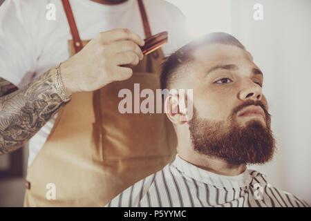 L'homme dans le processus de découpage d'un beard dans un salon de coiffure. Photo en style vintage Banque D'Images