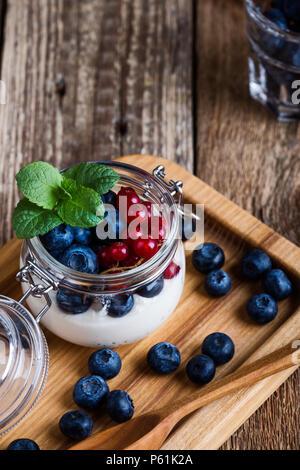 Les parfaits crème Cheesecake aux myrtilles et petits fruits groseille rouge servi dans un pot, sans cuisson d'été délicieux dessert sur la table rustique en bois prêt à manger Banque D'Images