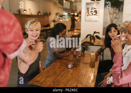 Group of smiling female friends ordering drinks dans un bistro Banque D'Images