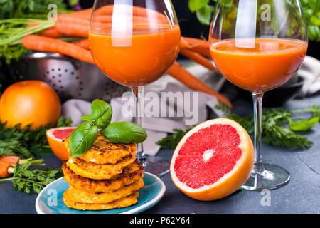 À partir de jus de carottes fraîches et de pamplemousse dans un verre et parfumé des crêpes pour le petit-déjeuner. vitamine boire pour un régime alimentaire sain. Les vitamines dans l'alimentation. Copy space Banque D'Images