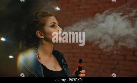 Belle jeune fille rousse fume une cigarette électronique. Elle se distingue par le mur de briques. Le soir le week-voyants clignotent. Banque D'Images