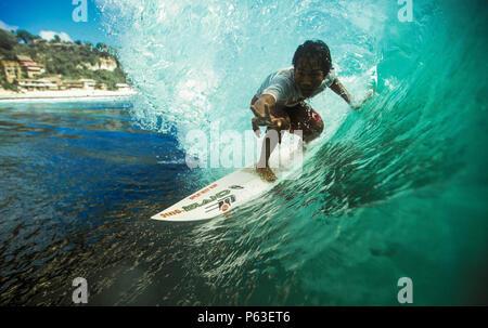 Surfer balinais équitation le fourreau de surf à l'onde verte, Bingin Bali Banque D'Images