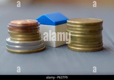 Le concept des prêts pour le logement. Maison blanche avec un toit bleu sur un tas de pièces de monnaie