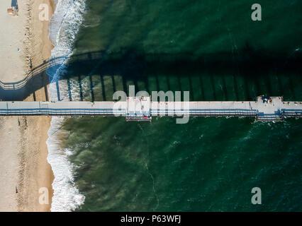 Une vue aérienne à 330 pieds/100 mètres sur un quai de Californie du sud situé sur une petite péninsule. Le fracas des vagues de mousse blanche et vibreur