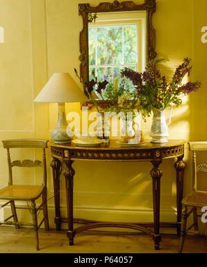 Miroir au-dessus de meubles anciens Table console avec la lampe jaune crème en pays hall Banque D'Images
