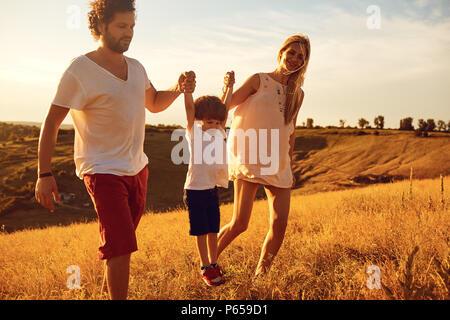 Happy Family having fun jouer au coucher du soleil. Banque D'Images