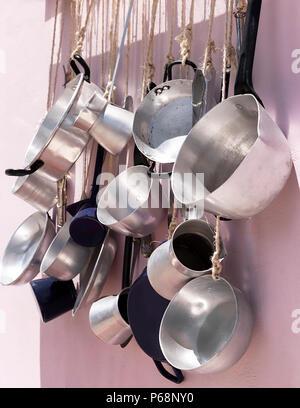 Cuisine Casseroles accrochée à un mur rose. Le point de droit. Banque D'Images