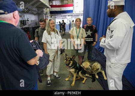 160525-N-QF605-036 NEW YORK (26 mai 2016) - Spécialiste en logistique 2e classe Erik Bryant fournit de l'information comme un guide pour les membres de l'oeil qui voit le programme de formation de chiot à bord de la classe Wasp-navire d'assaut amphibie USS Bataan (DG 5) pendant un navire tournée dans le cadre de l'intégration et la formation de désensibilisation pour les chiens à New York pour la Fleet Week New York (FWNY) 2016. L'oeil qui voit se reproduit plus de 500 chiots par année pour offrir des chiens pour aveugles et donne pour personnes aveugles dans l'utilisation, la manutention, et soin des chiens. FWNY, maintenant dans sa 28e année, est le lieu de l'honneur dans le temps Banque D'Images