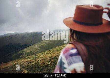 Et wanderlust travel concept. girl traveler holding hat et à la montagne. à hipster Femme avec sac à dos élégant, l'accent sur les montagnes dans les nuages. Banque D'Images