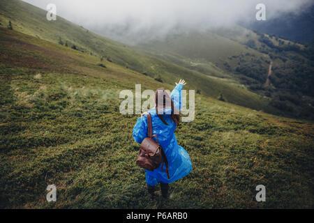 Et wanderlust travel concept. girl traveler avec sac à dos imperméable en balade dans les nuages dans les montagnes. hipster femme élégante d'explorer l'espace pour le texte. Banque D'Images