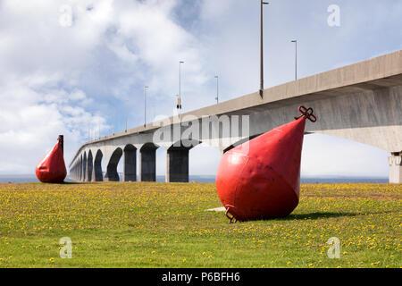 Des bouées métal rouge géant sur la pelouse en face de la huit mille de long Pont de la Confédération, qui relie l'île avec le Nouveau-Brunswick, au Canada. Banque D'Images