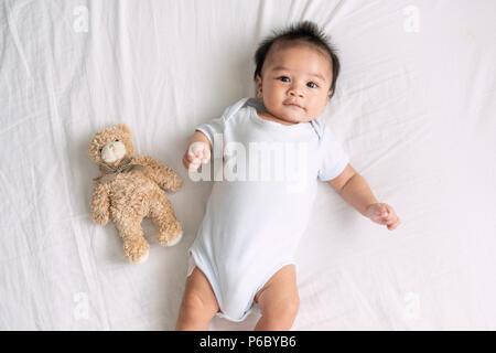 Portrait d'un bébé rampant sur le lit dans sa chambre, adorable bébé garçon dans chambre à coucher de soleil blanc, nouveau-né relaxing in bed, garderie pour les jeunes enfants Banque D'Images